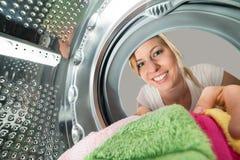 Donna sorridente che inserisce i vestiti in lavatrice Fotografie Stock Libere da Diritti