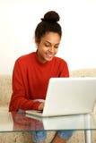 Donna sorridente che lavora dalla casa con il computer portatile Immagini Stock Libere da Diritti