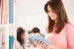 Donna sorridente che legge un libro Fotografia Stock