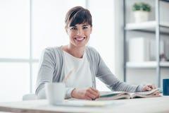 Donna sorridente che legge un libro Fotografia Stock Libera da Diritti