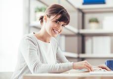Donna sorridente che legge un libro Fotografie Stock
