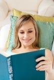 Donna sorridente che legge un libro che si trova su un sofà Fotografia Stock Libera da Diritti