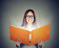 Donna sorridente che legge un libro con le lettere che volano via Fotografia Stock Libera da Diritti