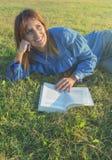 Donna sorridente che legge un libro in natura Fotografia Stock Libera da Diritti