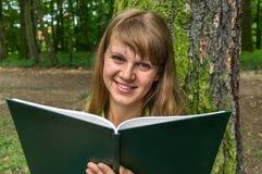 Donna sorridente che legge un libro nel parco Fotografie Stock Libere da Diritti