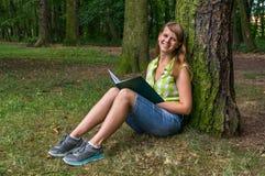 Donna sorridente che legge un libro nel parco Immagine Stock