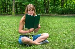 Donna sorridente che legge un libro nel parco Fotografia Stock Libera da Diritti