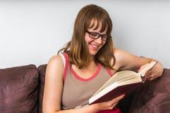 Donna sorridente che legge un libro nel salone Fotografia Stock