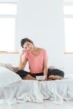 Donna sorridente che mangia i cereali con latte sul letto in camera da letto Immagini Stock