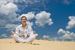 Donna sorridente che meditating sul deserto Fotografia Stock