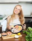 Donna sorridente che mette il limone dei pezzi nel pesce Fotografia Stock