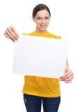 Donna sorridente che mostra l'insegna in bianco bianca di pubblicità Immagini Stock