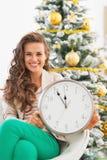 Donna sorridente che mostra orologio davanti all'albero di Natale Fotografia Stock Libera da Diritti