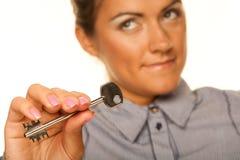 Donna sorridente che ostacola una chiave che appartiene alla sua casa fotografia stock