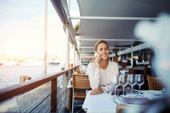 Donna sorridente che parla sul telefono cellulare mentre sedendosi alla tavola del ristorante comodo del marciapiede nel giorno s Immagine Stock