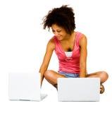 Donna sorridente che per mezzo dei computer portatili Immagini Stock Libere da Diritti