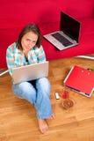 Donna sorridente che per mezzo del suo computer portatile Immagine Stock Libera da Diritti