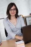 Donna sorridente che per mezzo del suo computer portatile all'ufficio Fotografie Stock