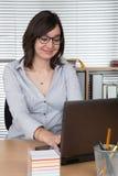 Donna sorridente che per mezzo del suo computer portatile all'ufficio Fotografie Stock Libere da Diritti
