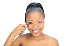 Donna sorridente che per mezzo delle pinzette Fotografia Stock