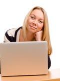 Donna sorridente che per mezzo di un computer portatile Fotografie Stock