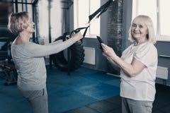 Donna sorridente che prende foto dell'amico che si esercita con l'istruttore della sospensione Fotografia Stock Libera da Diritti