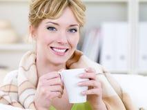Donna sorridente che scalda con la tazza Fotografia Stock