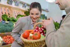 Donna sorridente che sceglie frutti differenti all'esposizione degli alimentari dell'azienda agricola immagini stock libere da diritti