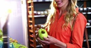 Donna sorridente che seleziona le mele verdi nella sezione organica video d archivio
