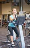 Donna sorridente che si esercita sulla bici di esercizio in palestra Fotografia Stock Libera da Diritti