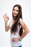 Donna sorridente che si leva in piedi con le braccia piegate Fotografia Stock