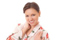 Donna sorridente che si leva in piedi su una priorità bassa bianca Fotografie Stock