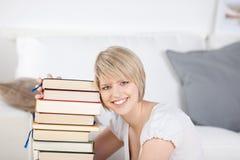Donna sorridente che si rilassa a casa con i suoi libri Immagini Stock