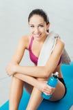 Donna sorridente che si rilassa dopo l'allenamento Fotografia Stock