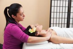 Donna sorridente che si rilassa durante il massaggio posteriore alla stazione termale Fotografie Stock