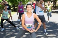 Donna sorridente che si scalda prima della corsa Fotografie Stock Libere da Diritti