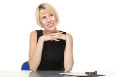 Donna sorridente che si siede alla tabella Immagini Stock