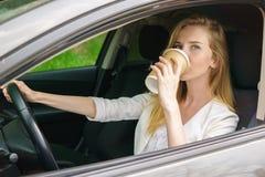 Donna sorridente che si siede in automobile fotografia stock