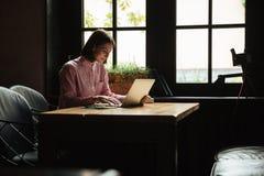 Donna sorridente che si siede dalla tavola in caffè e nel per mezzo del computer portatile Immagini Stock Libere da Diritti