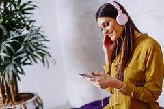 Donna sorridente che si siede e che ascolta la musica sulla cuffia avricolare Immagini Stock Libere da Diritti