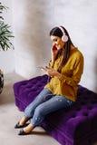 Donna sorridente che si siede e che ascolta la musica sulla cuffia avricolare Fotografia Stock Libera da Diritti
