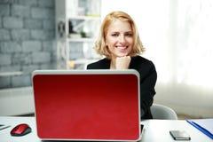 Donna sorridente che si siede nel suo luogo di lavoro Immagine Stock