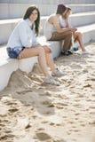 Donna sorridente che si siede sui punti alla spiaggia immagine stock