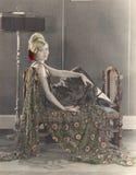Donna sorridente che si siede sul divano Fotografie Stock