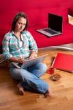 Donna sorridente che si siede sul pavimento Fotografia Stock Libera da Diritti