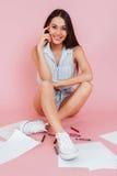 Donna sorridente che si siede sul pavimento con i fogli di carta Immagini Stock Libere da Diritti