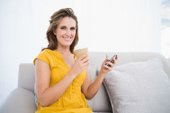 Donna sorridente che si siede sul sofà che fora caffè e per mezzo del telefono Immagini Stock