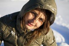 Donna sorridente che si siede sulla neve fotografie stock libere da diritti