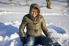 Donna sorridente che si siede sulla neve fotografia stock libera da diritti