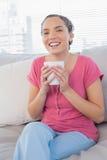 Donna sorridente che si siede sulla tazza della tenuta del sofà di caffè Fotografia Stock Libera da Diritti